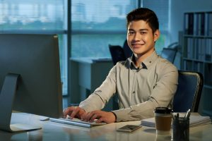 smiling filipino sitting infront of desk